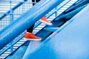 persona subiendo una escalera con zapatillas deportivas